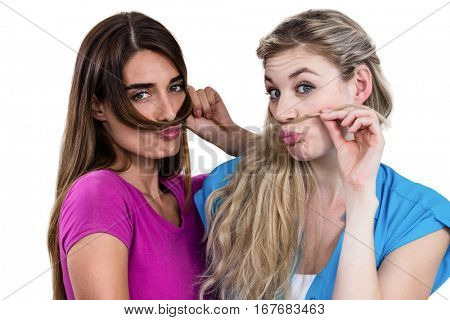 Portrait of mischievous friends playing with hair on white background