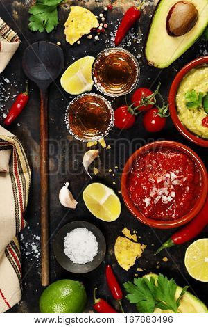 Mixed mexican food background. Party food. Guacamole,nachos, salsa, peppers, tomatoes, avocado and tequila shots on a rustic table.Top view. Tex-mex cuisine. Assorted appetizers. Food frame