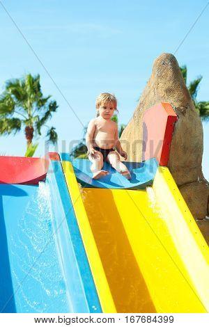 Cute Baby Boy Sits On Top Of Waterslide