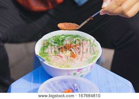 Man Hands Putting Chili Soup Into Pho, The Vietnamese Noodle Soup. Pho Is The Most Famous Food In Vi