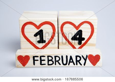 Valentine's day.Wooden cubes with handwritten one and four inside red hearts, February. Empty space.