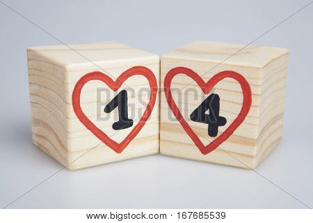 Valentine's day. Wooden cubes with handwritten one and four inside red hearts.