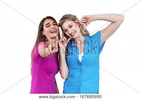 Portrait of smiling female friends gesturing on white background