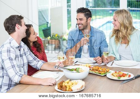 Smiling friends holding wine glasses while sitting at table