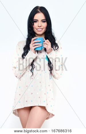 pretty woman or cute sexy girl with long brunette hair and smiling face in nightie shirt holds coffee or tea cup isolated on white background
