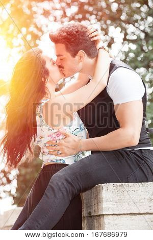 Beautiful couple kissing and love. Loving relationship and feeling. Passionate kiss. A man and a woman is strongly embrace with passion and feeling. Bright light that illuminates the scene.