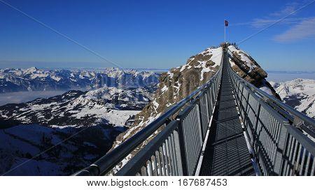 Winter scene in the Swiss Alps. Suspension bridge connecting two mountain peaks on 3000m altitude. View from the Glacier de Diablerets ski area.