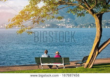 Couple on bench beside lake. Tree, sunlight and water. Peace of mind and love.