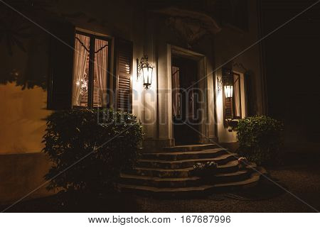 Door of house at night. Bushes near stone stairs. Expensive real estate in Italy.
