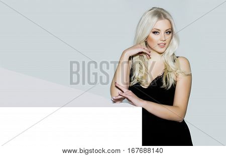 pretty girl or cute smiling woman with long platinum blonde hair and fashionable makeup on face in sexy glamour black dress on white and grey background copy space
