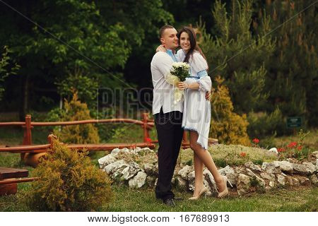 Groom In An Embroidered Blue Shirt Hugs A Tender Brunette Bride Standing On The Green Grass