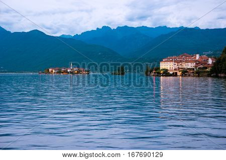 Mountains, water and sky. Island and buildings at distance. Tour to Isola Superiore.