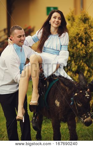 A Picture Of A Pretty Brunette Sitting On The Donkey And A Man In Embroidered Shirt Holding Her