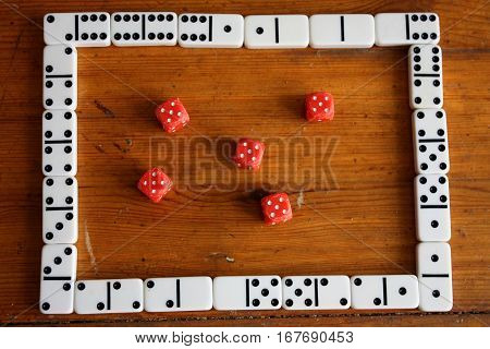 Classic red poker dices framed with domino game pieces on brown wooden background