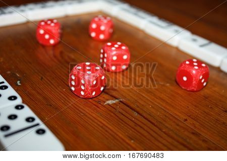 Classic red poker dices close up on wooden brown background with domino game frame