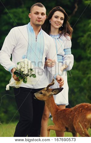 Pretty Wedding Couple In Embroidered National Dressing Stands In The Forest While A Little Deer Trie