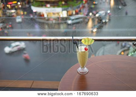 Selective Focus On Glass Of Juice Against Street Cityscape On Background. Concept Of Spending Leisur