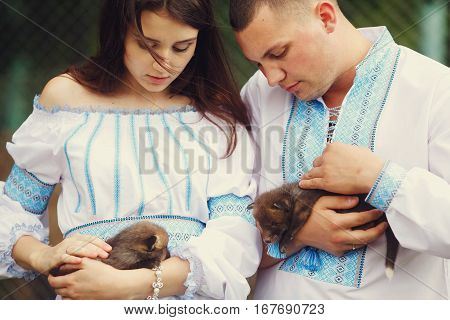 Picture of a wedding couple dressed in ethnic style with little polecats in their arms