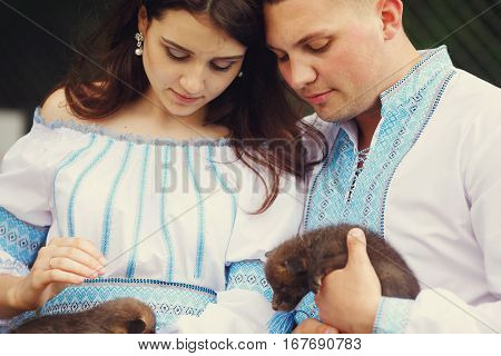 Man and woman dressed in blue embroidered shirts stroke little polecats