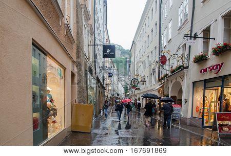 SALZBURG AUSTRIA - JUNE 12 2012: People walking at Salzburg central shopping street Getreidegasse in rainy day