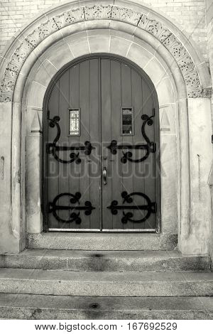 Beautiful image of old stone church with heavy wood doors and elaborate hardware