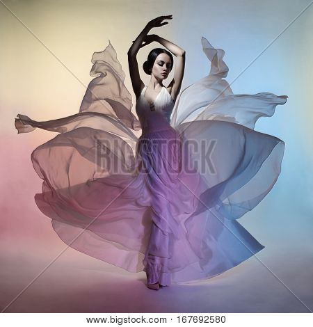 Art fashion studio photo of beautiful elegant woman in blowing dress. Flying dress. Freedom concept