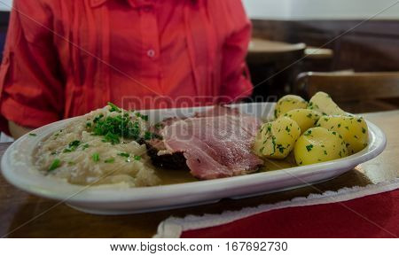Traditional Smoked Pork Neck With Boiled Potatoes And Fried Sauerkraut On A Plate At Cafe In Salzbur