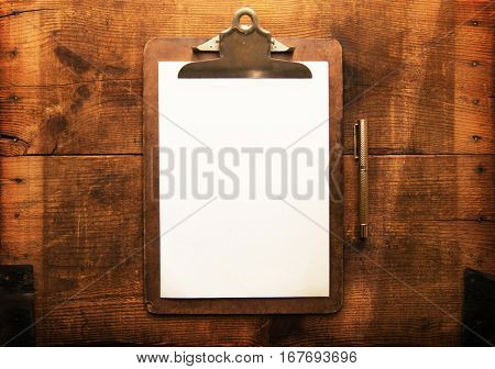 Old clipboard with blank white paper and pen on rustic and grungy wooden surface, with plenty of copy space.