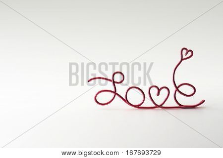 "Cute and simple ""LOVE"" background with rising hearts, made from hand shaped red wire. Natural white background."