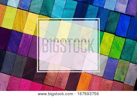 "Cover for creative works. Spectrum of multi colored wooden blocks with white area with ""Creative  Works"" text . Background or cover for something creative or diverse."
