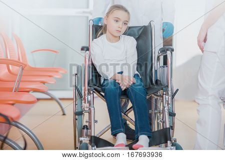Wheelchair Disability in Children. Mobility Impairments. Young Caucasian Girl on the Wheelchair in the Hospital Hall with Physicians in the Background.