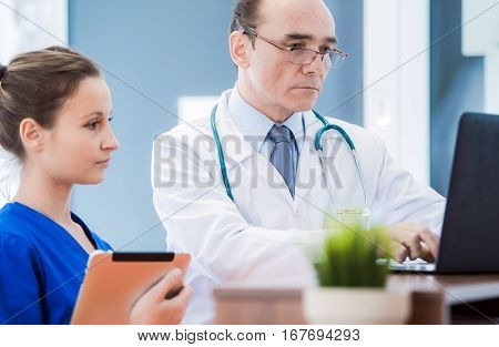 Caucasian Male Medical Doctor Consulting Current Issues with Female Medical Practitioner. Examining Xray Imagery on the Laptop Computer.
