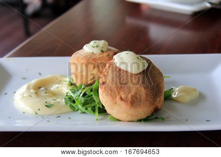 Simple white plate with two freshly baked crab cakes, flavorful dipping sauce and greens aside of them.