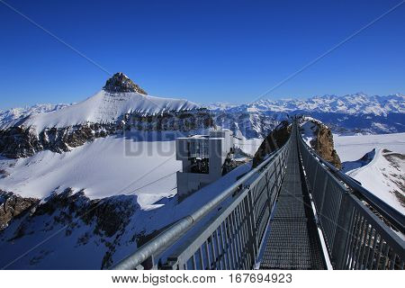 Winter scene on the Glacier des Diablerets. Mount Oldenhorn. Suspension bridge connecting two mountain peaks. Summit station of a cable car.