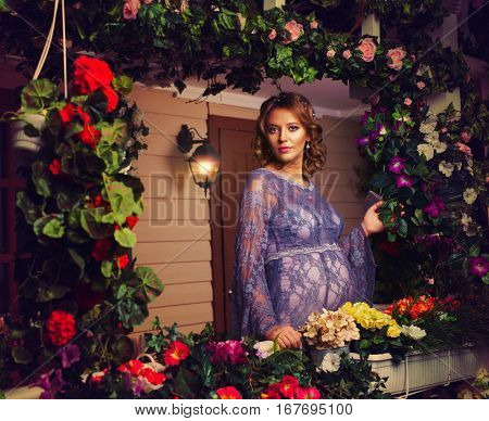 Young pregnant woman tender portrait at house with lots of flowers