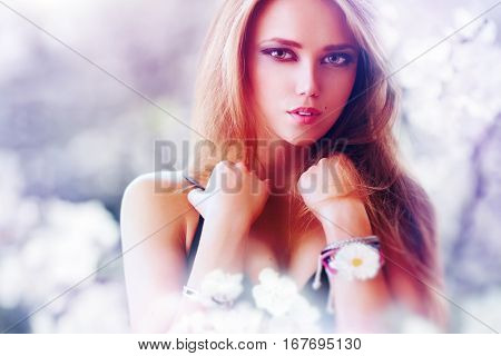 Young sexy woman portrait in anime style with big eyes. Bright soft colors of blooming flower garden.