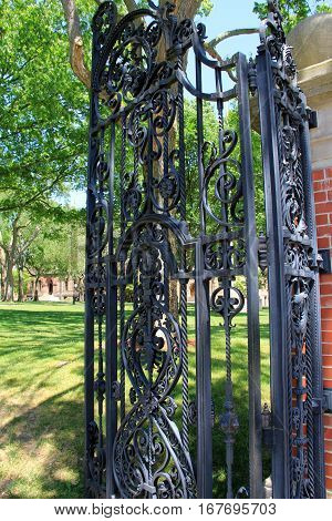 Beautiful detail of large, black, wrought-iron gate that opens to  lawns beyond.