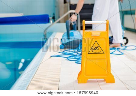 Swimming Pool Cleaning Time. Watch For Slippery Tile Floor Yellow Warning Sign.