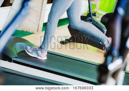 Treadmill Fitness Running Closeup Photo. Female Running on the Treadmill in the Fitness Center.