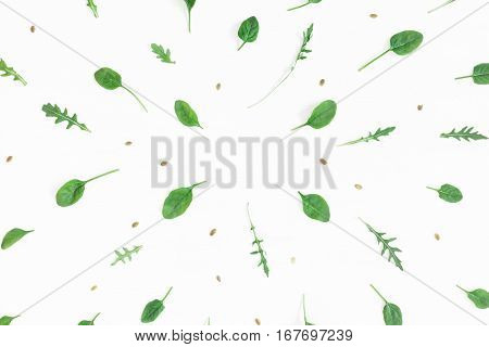 Frame made of arugula spinach leaves on white background. Flat lay top view