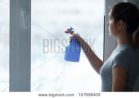 The Young Girl Carefully Washes And Cleans A Window.