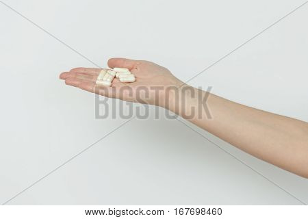 Hand Is Giving Capsules On White Background.