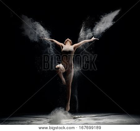 Slender girl dancing in white powder cloud jumping and streching up studio shot