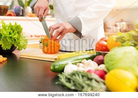 cook preparing vegetable salad in domestic kitchen