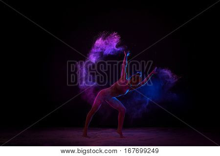 Slender girl in beige bodysuit dancing in cloud of pink and blue dust bending gracefully studio shot