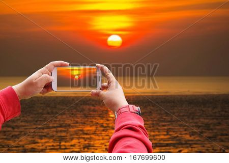 Smartphone Concept Smartphone photographing big sunset on the beach Similan Island Koh Ta Chai Andaman Sea Thailand