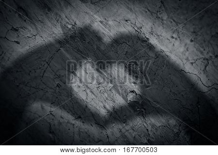 Shape of a love heart created by human hand on the rough wall.