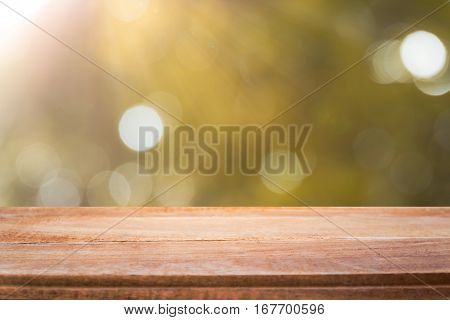 table and sunlight bokeh with blurred trees background empty wooden table for product display