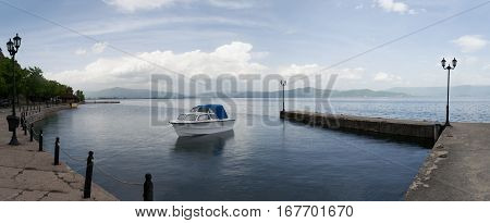 Speedboat docked on peaceful blue lake port on cloudy day