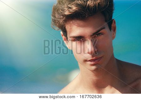 Man confident gaze, handsome face model. Hair style. Blue background. A close portrait of a beautiful boy, a young man with stylish hair. Intense gaze. Without T-Shirt.